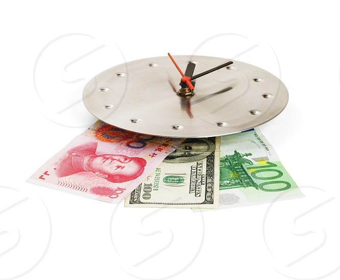 currency bills on a stainless steel clock clock isolated on white back ground photo