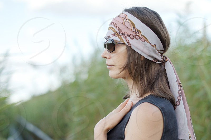 Bohemian woman with a head scarf and sun glasses outdoors in the wilderness on wooden path leading through reed field photo