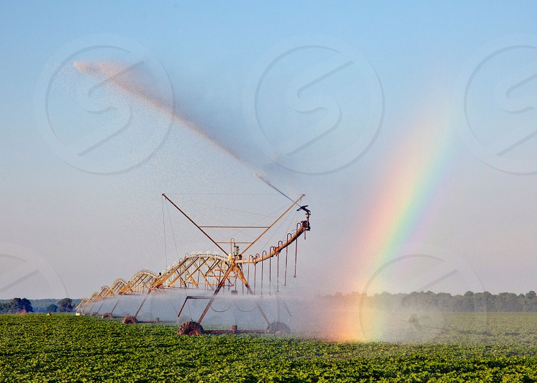 Rainbow at the end of a combine of a soybean farm photo