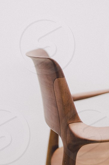 brown wooden armchair beside white wall photo