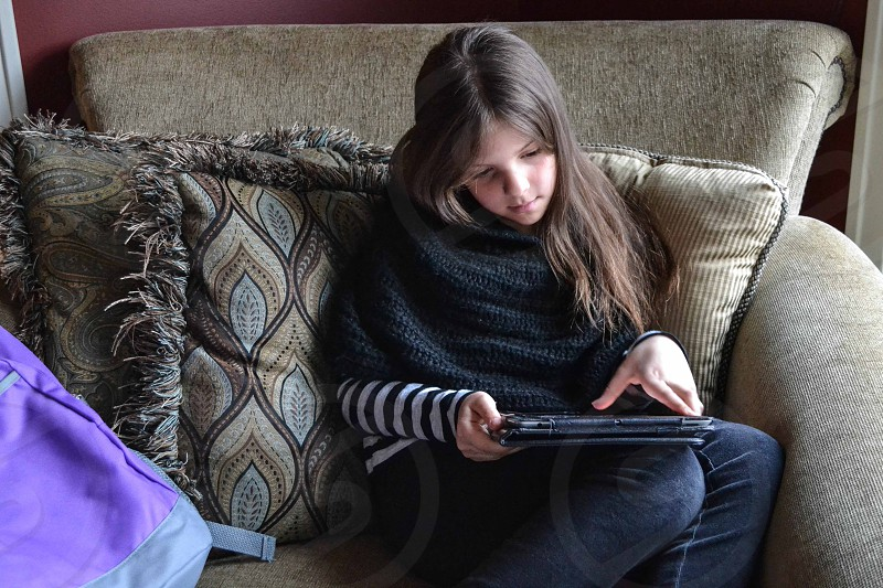 girl in chair with ipad photo