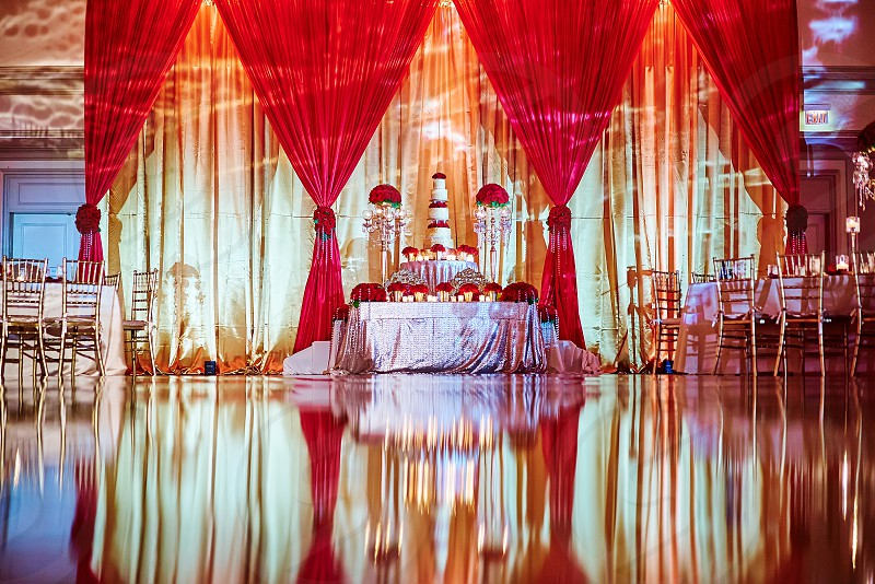 The luxury red roes theme of weding dinner table decorated with a bunch of red roses in the center and surround with small vase of red roses and candle light. photo