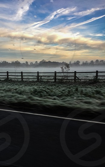 Amazing view I saw whilst driving action shot. The morning fog contrasts perfectly with the early sunrise.  photo