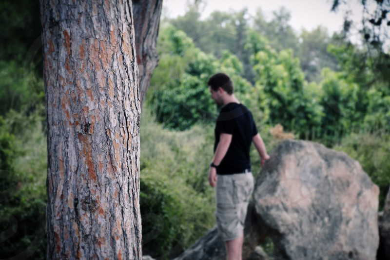 Young man in the forest in blur background .Concept of lost man or in thoughts. photo
