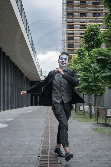 Male young cosplayer wearing business casual suit happily walking in the street front view portrait photo
