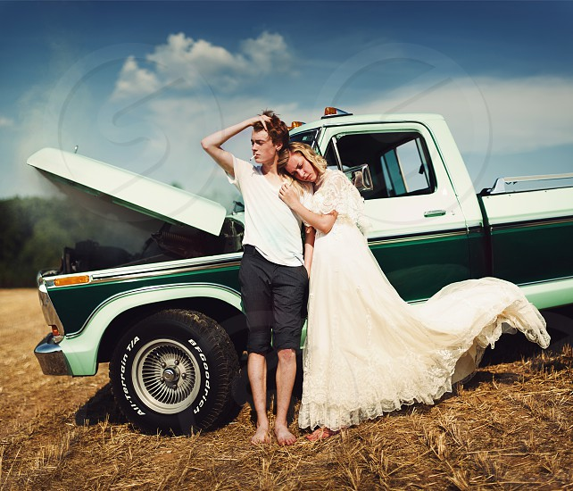 woman in white gown beside man in black capri pants leaning on white and green pick up truck photo