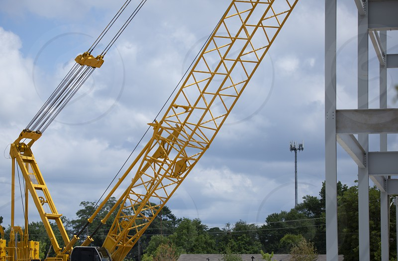 Construction crane and the edge of newly erected steel beams photo