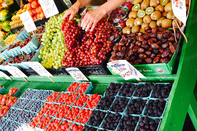 Fresh fruit organic market produce vibrant colorful berries grapes hands sorting  photo