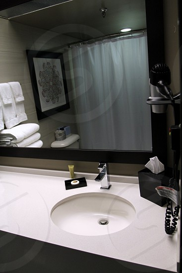 Black and gray hotel bathroom with vanity and reflection of shower curtain photo