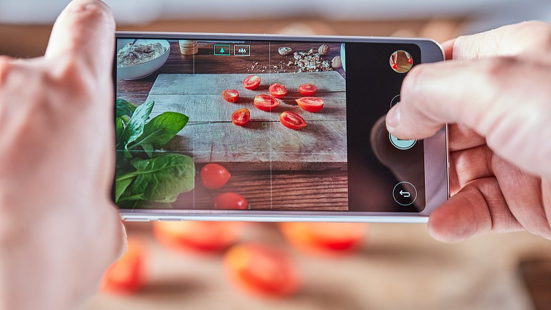 Woman's hands are shooting on a smartphone photo of sliced tomatoes on a wooden board. Home made food photo for social networks. photo