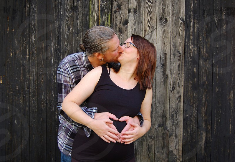woman in black tank dress kissing lips with man in black grey checked dress shirt with their hands on woman's tummy near grey black wooden wall photo