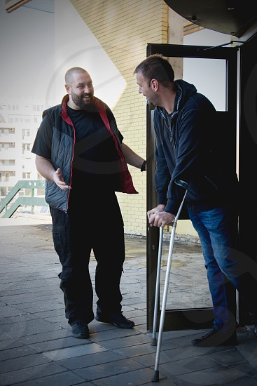 Man opening door and helping another man on crutches photo