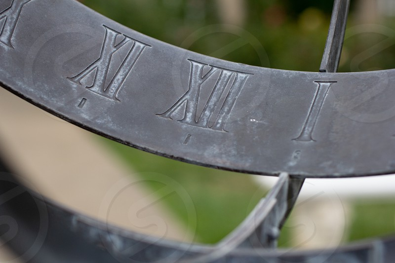 A closeup view of a metal sundial in the garden photo