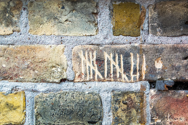 Number thirteen written in tally marks on a colorful brick wall photo