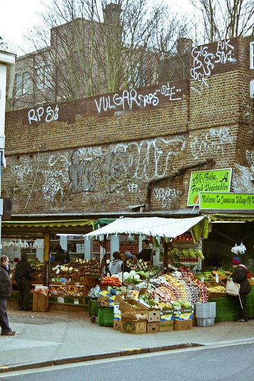 fruit stand near brown bricked wall photo