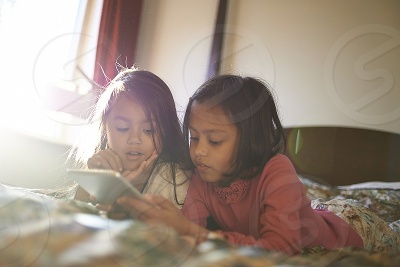Two cute young Asian sisters playing together laying down on bed using an iPad with the sunlight coming in through the window photo