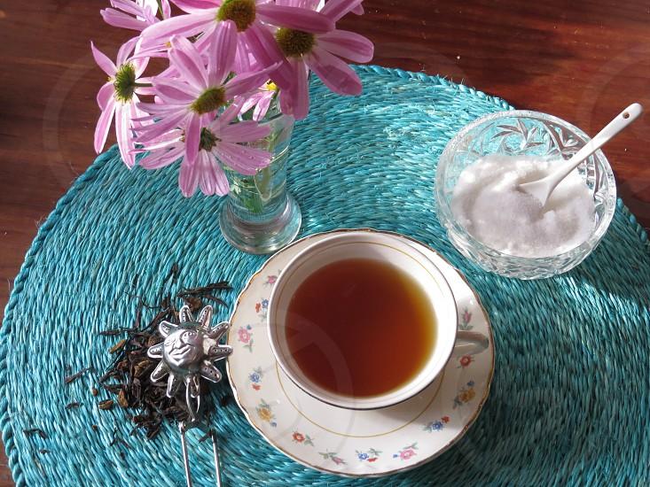 Cup of tea with tea leaves sugar flowers photo