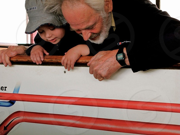 Grandpa and son watching engine of a boat.  photo