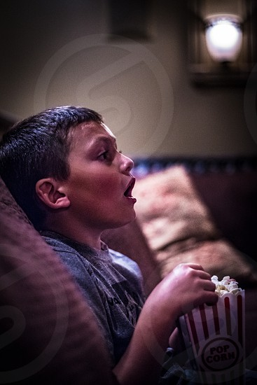 Kid watching a movie and eating popcorn in a home movie theater setting. 7 year old boy. photo