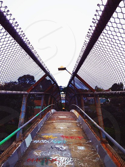 gray metal foot bridge with graffiti photo