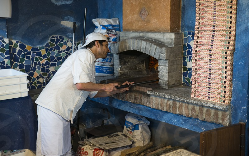 Golfo Aranci09-April-2018Chef making a pizza in an original wood-fired pizza oven in Golfo Aranci this place is famous on sardinie of the coastline and the dolphins photo