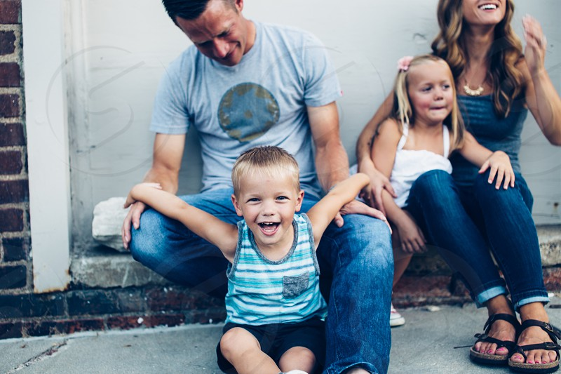 smiling boy sitting in front of man in blue jeans beside girl and woman photo