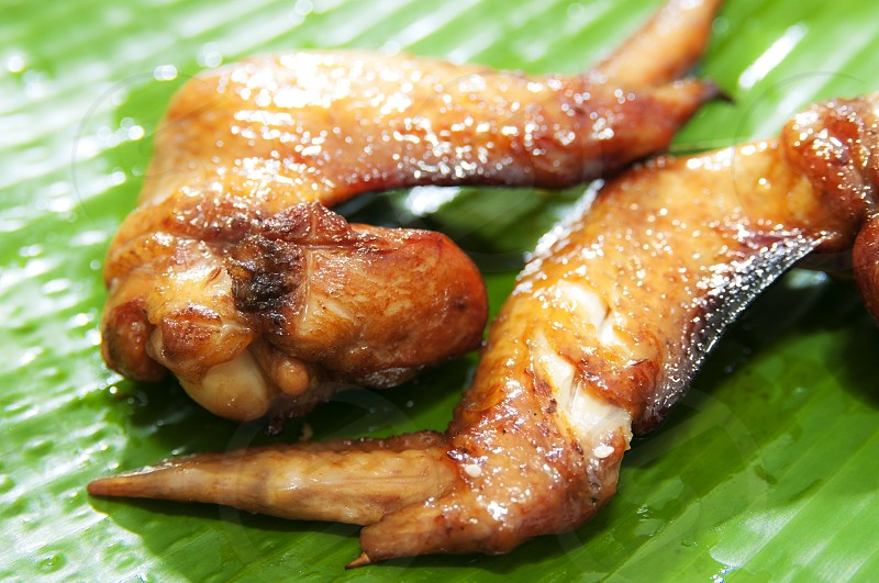 Closeup of barbecue chicken wings on banana leaf photo