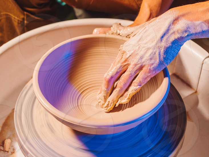Creating earthenware and traditional pottery concept. Experienced male potter's hands creating beautiful clay product - bowl - using professional tools. Toned cinematic craft factory authentic. photo