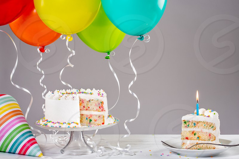White Buttercream birthday cake with colorful balloons and hat. photo