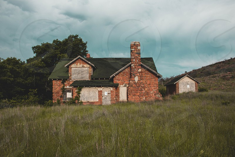 An abandoned cabin in the mountains. Storms brewing behind it. photo
