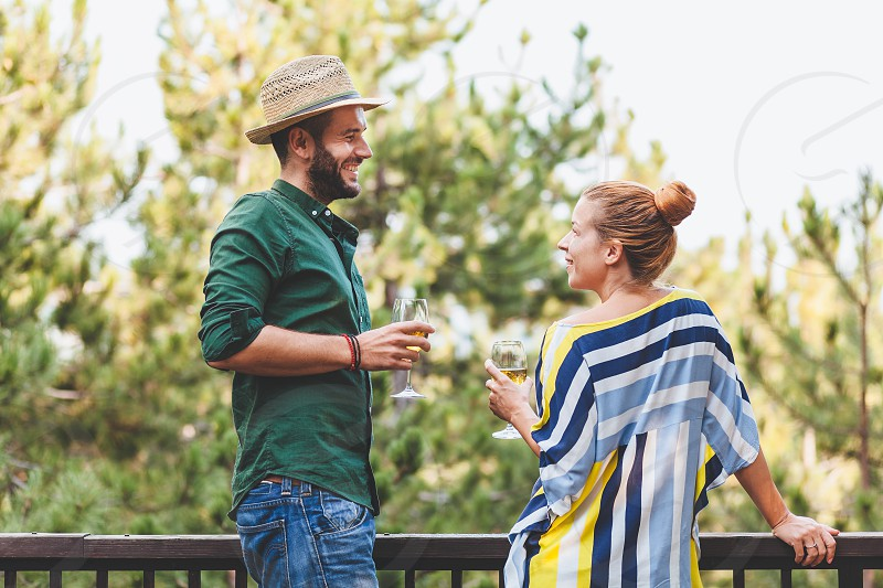 Young couple flirting on the balcony drinking white wine photo