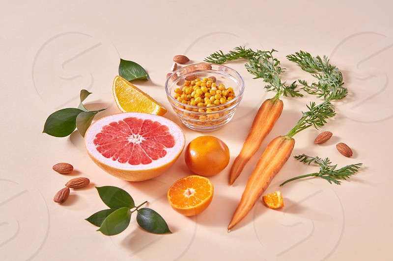 Organic vegetarian ingredients for cooking healthy smoothie - orange vegetables and fruits on an orange paper background. Healthy dietary eating. photo
