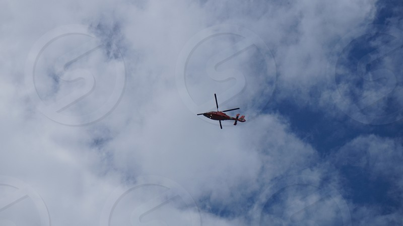 low angle photography of black helicopter above the sky photo