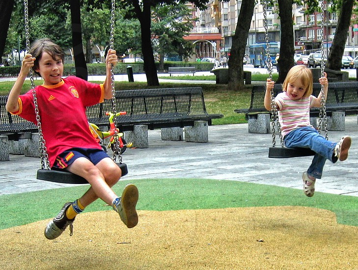 boy and girl riding on metal swing photo