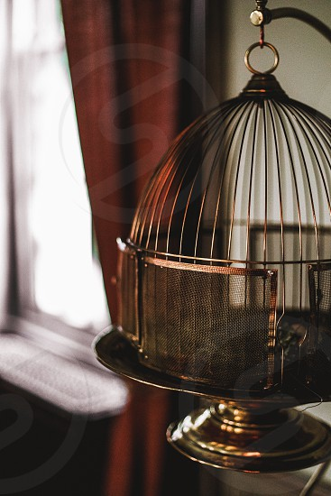 An antique bird cage by a window.  photo