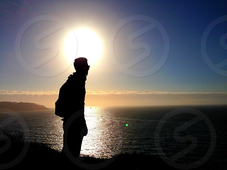 man standing on cliff silhouette photo photo