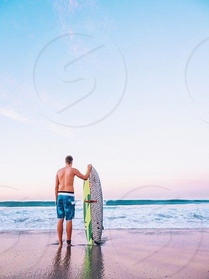 man holding surf board on shore photo