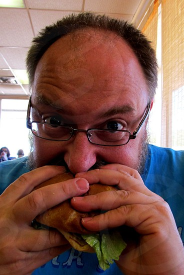 Balding man with crew cut and glasses eats a burger photo