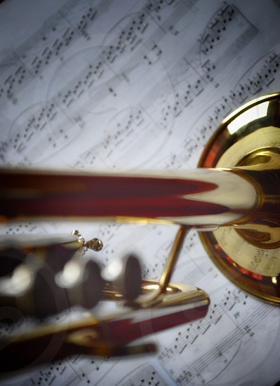 close up shot of brass trumpet near music sheet photo