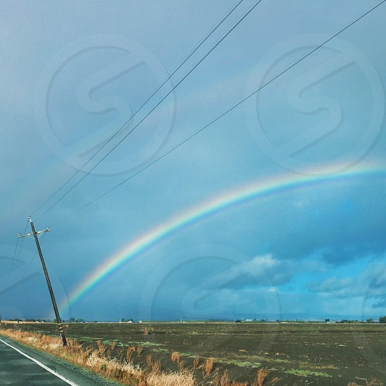 rainbow over brown soil photo