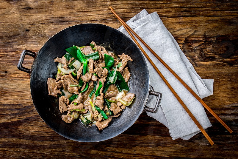 Traditional chinese mongolian beef stir fry in chinese cast iron wok with cooking chopsticks wooden background. Top view copy space. photo