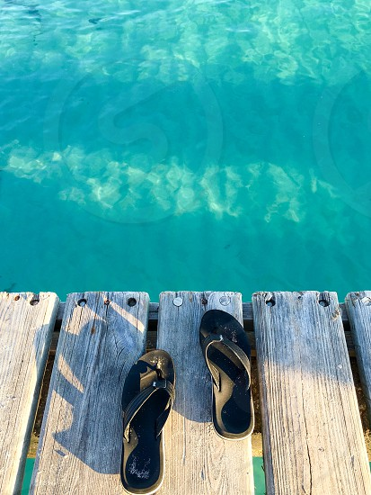 A pair of flip-flops on a pier with Caribbean sea in the background photo