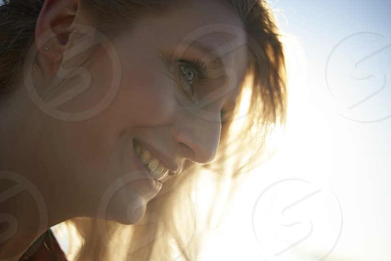 Close up portrait of a young caucasian woman with piercing blue eyes taken outdoors in winter sunshine near a lake photo