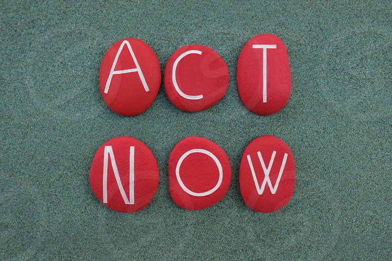 Act Now slogan Climate Emergency protest sign composed with red colored stones over green sand photo