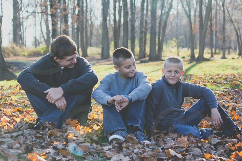 boys in blue denim jeans sitting on dried leaves on ground photo