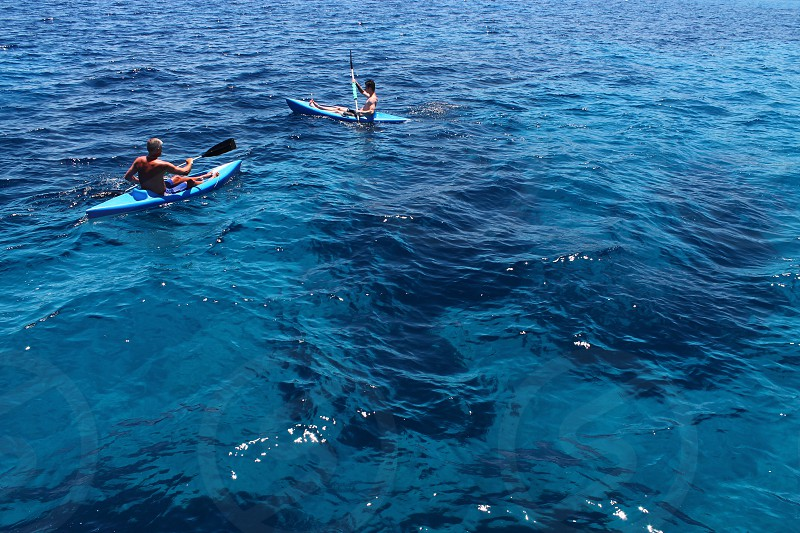 Kayak water ocean sea uneven surface kayaking men unrecognizable rear view kayaks padling canoe canoeing canoes blue minimal minimalism activity activities summer vacation holiday fun sport two people sunlight sun sunny day daylight day outdoor outdoors photo