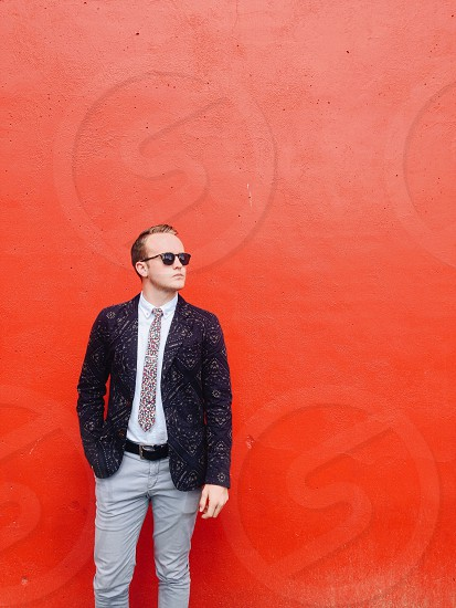man in grey pants and blue blazer standing in front of orange wall photo