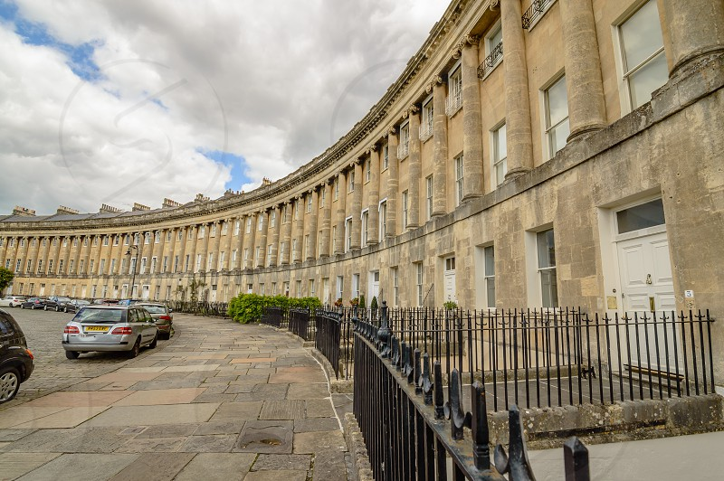 Royal Crescent in Bath. The Royal Crescent is a row of 30 terraced houses laid out in a sweeping crescent in the city of Bath England. Designed by the architect John Wood. photo