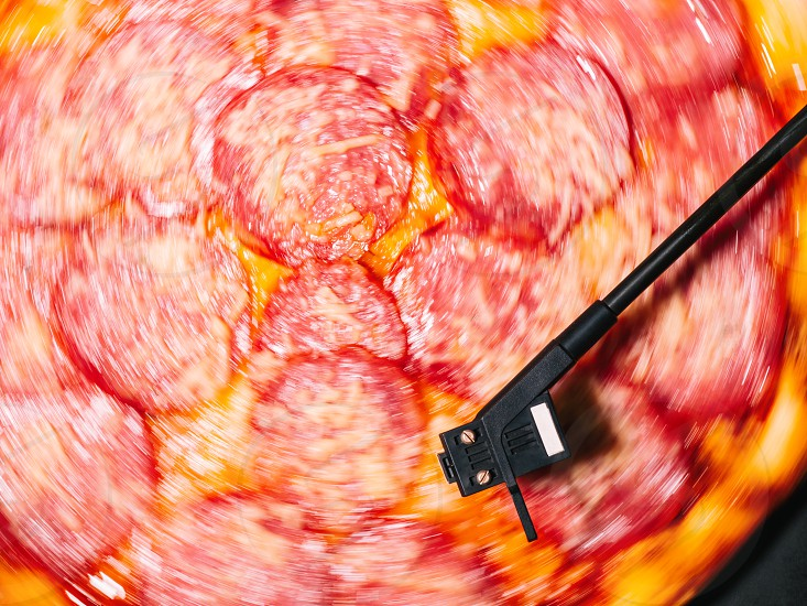 Party with delicious junk food. Italian pizza with salami sausage and cheese spinning on turntable vinyl player as vinyl record. photo