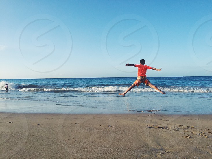 Jumping sky blue beach vacations happy colorful kids fun beach day ocean tropical  photo